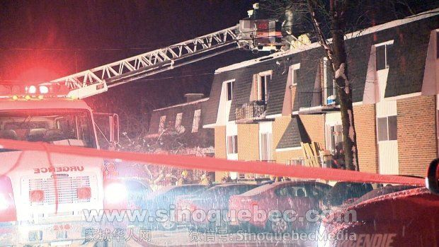 Firefighters are on scene of a blaze in an apartment building in western Quebec on Tuesday, Dec. 23, 2014.